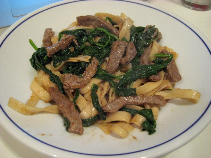 Fried noodles with beef and spinach in Chinese BBQ sauce