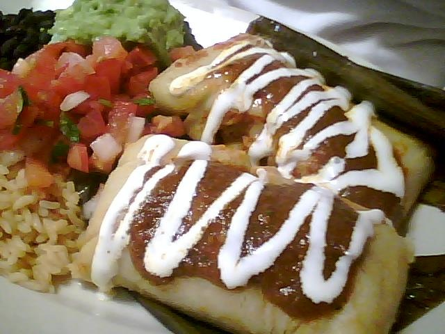 Chicken tamales with red sauce, served with rice, beans, salsa, and guacamole