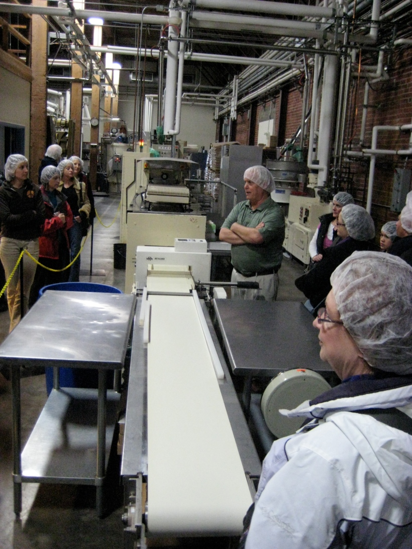 """After tempering (melting the cocoa powder into liquid form), the chocolate gets molded and passed along this assembly line.  Just like in """"I Love Lucy"""""""