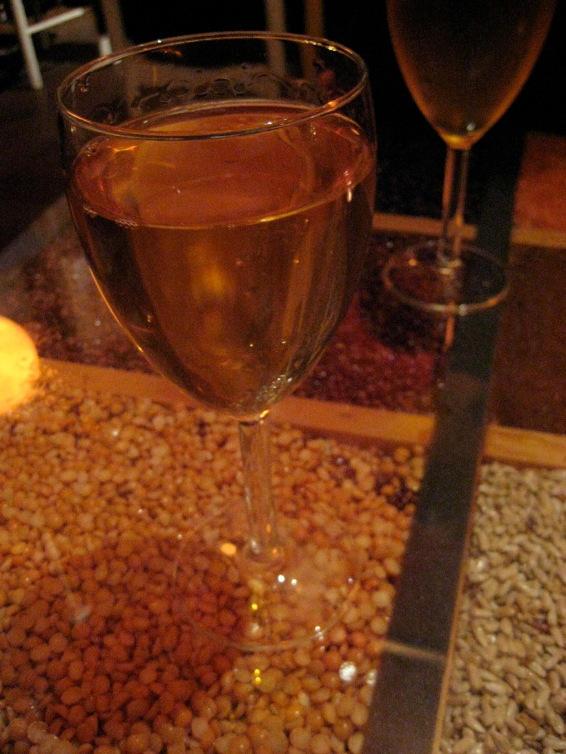 Honey Wine, on top of the glass table filled with various Ethiopian grains