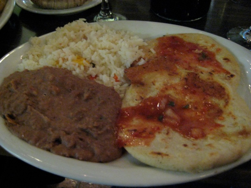 Two pork and cheese pupusas topped with salsa, served with beans and rice.