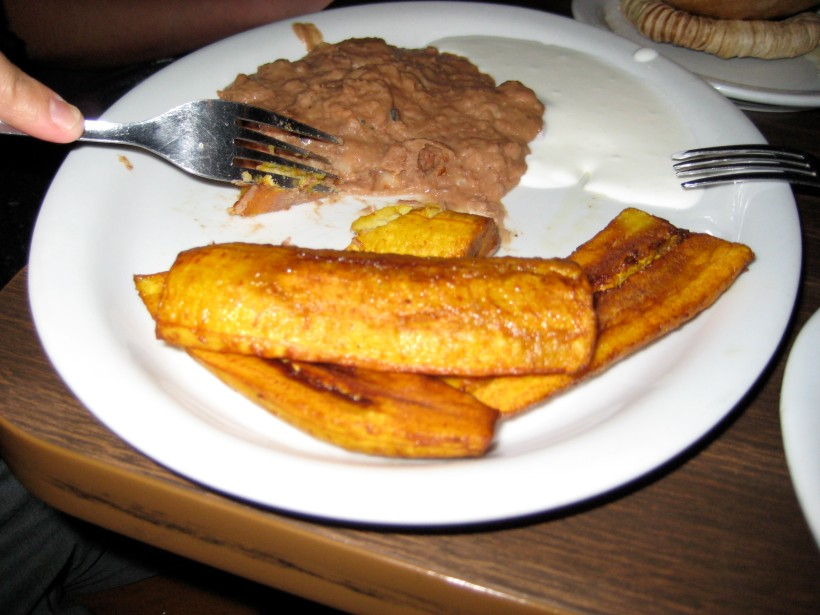 Fried plantains, served with beans and crema.