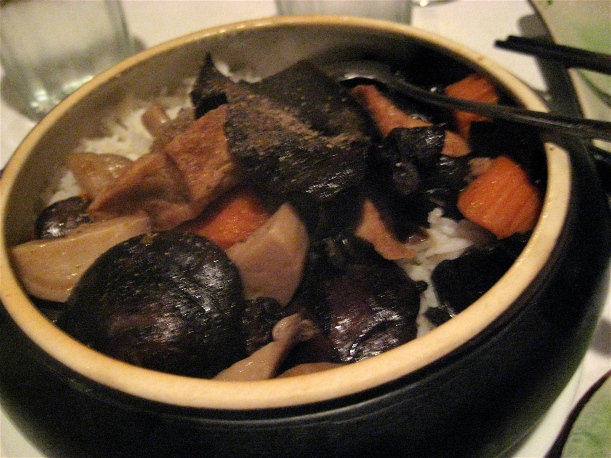 Braised mushrooms and tofu over rice in a claypot.