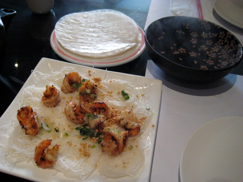 Grilled shrimp on a bed of vermicelli saucers, with rice paper and hot water.